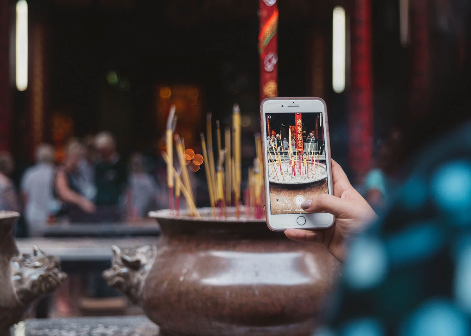 Photo of iPhone taking photo of incense burning at Ong Bon Pagaoda