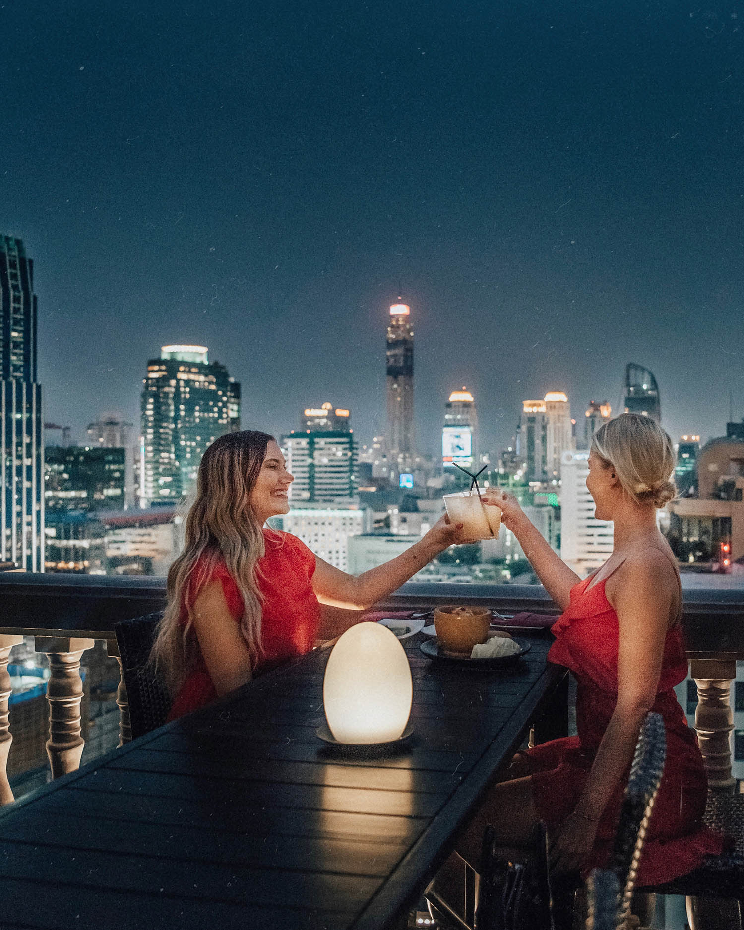 What to Wear in Thailand: Two girls in red dresses sharing a toast - Rooftop Bar at Muse Hotel in Bangkok
